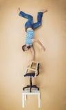 Hombre en una pila de sillas Imagen de archivo libre de regalías