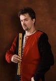 Hombre en una pizca medieval del juego una flauta Imágenes de archivo libres de regalías
