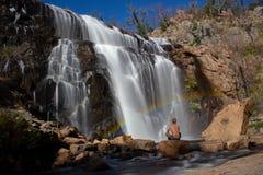 Hombre en una roca debajo de un arco iris delante de la cascada, Mackenzie Falls, Australia imagen de archivo libre de regalías