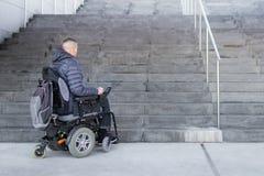 Hombre en una silla de ruedas que mira las escaleras imágenes de archivo libres de regalías