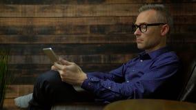 Hombre en una silla suave usando la tableta almacen de metraje de vídeo
