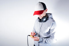 Hombre en una sudadera con capucha gris en una música que escucha del fondo blanco de un smartphone en auriculares grandes Foto de archivo libre de regalías
