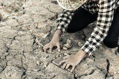 Hombre en una tierra azotada por la sequía en esperanzas fotos de archivo