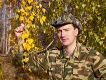 Hombre en uniforme en bosque del otoño Fotografía de archivo