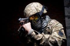 Hombre en uniforme militar con el arma en su mano fotos de archivo
