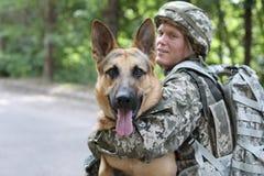 Hombre en uniforme militar con el perro de pastor alemán imagenes de archivo