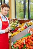 Hombre en verduras que ordenan de la tienda de alimento biológico Fotos de archivo libres de regalías