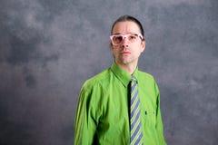 Hombre en vidrios verdes del rosa de la camisa en la cabeza que parece escéptica Imágenes de archivo libres de regalías