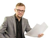 Hombre en vidrios y chaqueta con los documentos en su mano que sonríe para mirar la cámara aislada en el fondo blanco fotos de archivo libres de regalías