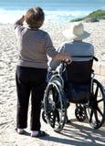 Hombre en wheelcheair en la playa imagenes de archivo