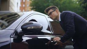 Hombre encantado en el traje que frota ligeramente el coche y que entra, ganando el dinero para la compra almacen de metraje de vídeo