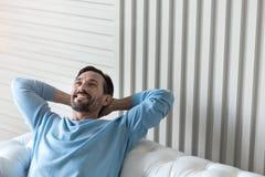 Hombre encantado feliz que lleva a cabo sus manos detrás de la cabeza Fotografía de archivo libre de regalías