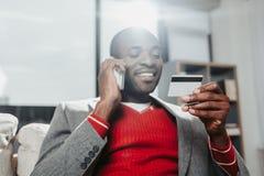 Hombre encantado que charla por el teléfono móvil y la tarjeta de banco de examen fotografía de archivo libre de regalías