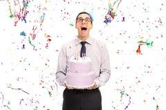Hombre encantado que sostiene una torta de cumpleaños Imagen de archivo