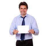 Hombre encantador que sonríe y que le muestra una tarjeta Imagen de archivo libre de regalías