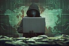 Hombre encapuchado con la máscara anónima usando el ordenador portátil a cortar el banco Imagen de archivo libre de regalías