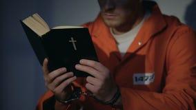 Hombre encarcelado en esposas que lee la biblia, sintiendo culpable y rogando para el alma metrajes