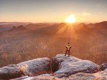 Hombre encima de la montaña El caminante subió en el pico de la roca sobre el valle Imagen de archivo