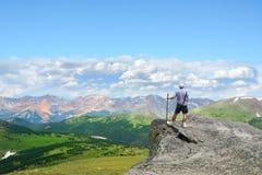 Hombre encima de la montaña que mira hermosa vista Imágenes de archivo libres de regalías