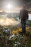 Hombre encima de la montaña que mira la estrella de la Navidad imagen de archivo