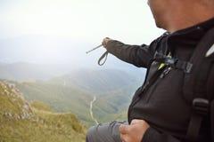 Hombre encima de la montaña que señala en algo Imagenes de archivo