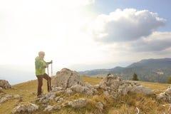 Hombre encima de la montaña que señala en algo Fotografía de archivo libre de regalías