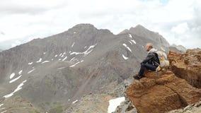 Hombre encima de la montaña que se sienta en la roca que mira una salida del sol agradable en el pueblo almacen de metraje de vídeo