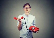Hombre enfadado confuso del adolescente con el teléfono pasado de moda Foto de archivo libre de regalías