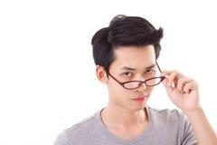 Hombre enfadado del empollón del genio que le mira, mano que lleva a cabo el eyeglasse Imagenes de archivo