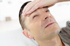 Hombre enfermo con dolor de cabeza en el sofá Fotos de archivo libres de regalías