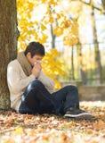 Hombre enfermo con el tejido de papel en parque del otoño Imagen de archivo libre de regalías