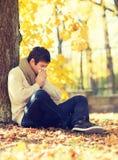 Hombre enfermo con el tejido de papel en parque del otoño Foto de archivo libre de regalías