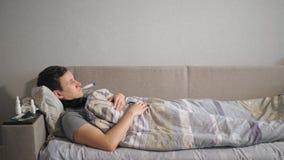 Hombre enfermo con el termómetro que miente en el sofá almacen de metraje de vídeo