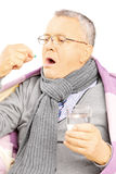Hombre enfermo cubierto con la manta que toma una píldora Imagen de archivo libre de regalías