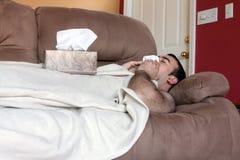 Hombre enfermo en el sofá Fotos de archivo