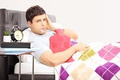 Hombre enfermo en la cama que tiene un dolor de cabeza con el termómetro en su boca Imagen de archivo libre de regalías