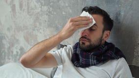 Hombre enfermo preocupante que limpia la frente con el tejido almacen de video