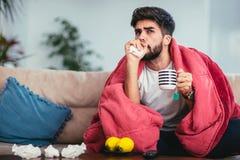 Hombre enfermo que bebe té caliente en casa y que ve la TV foto de archivo libre de regalías