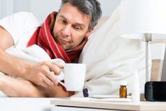 Hombre enfermo que come café en cama Imagen de archivo