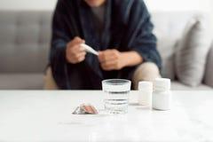 Hombre enfermo que miente en el sof? que comprueba su temperatura en casa en la sala de estar fotos de archivo libres de regalías