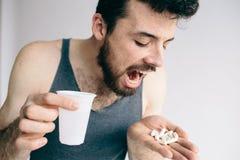 Hombre enfermo que sostiene píldoras en un fondo blanco Imagen de archivo