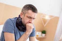 Hombre enfermo que tiene una garganta dolorida foto de archivo