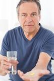 Hombre enfermo que toma sus píldoras Foto de archivo