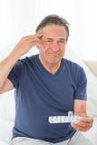 Hombre enfermo que toma sus píldoras Imágenes de archivo libres de regalías