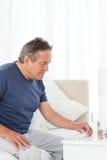 Hombre enfermo que toma sus píldoras Fotos de archivo libres de regalías