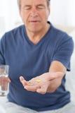 Hombre enfermo que toma sus píldoras Imagen de archivo