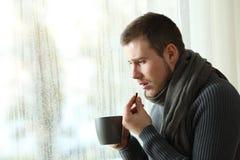 Hombre enfermo que toma una píldora del calmante en un día lluvioso de invierno Imágenes de archivo libres de regalías