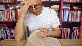 Hombre enfocado en el libro de lectura de los vidrios que se sienta en la tabla con la lámpara en la biblioteca casera almacen de metraje de vídeo