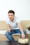 Hombre enfocado que juega al videojuego que sostiene la palanca de mando y que come popco Fotos de archivo libres de regalías