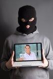 Hombre enmascarado con el ordenador con la imagen de la mujer que da el dinero Imagen de archivo